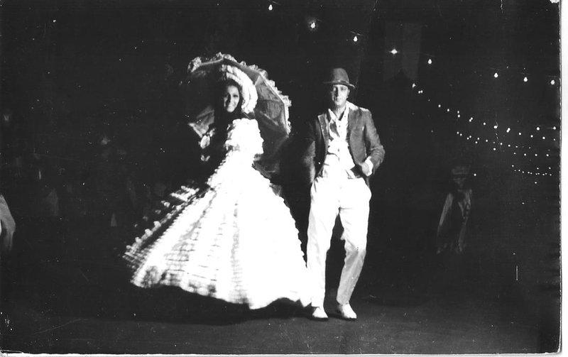 Sandra Castiel e Dilson Machado, na passarela, olhos nos olhos, dirigidos por Marise Castiel. Sóbrios, discretos, elegantes, belíssimos, faziam praticamente o apogeu, o ápice, o luxo monumental naquela ópera, que se apresentava na avenida a céu aberto em Porto Velho, não no palco do Teatro Amazonas. Aplausos, aplausos. O público torcia também para outros destaques, a platinada e deslumbrante Bebeth, Kicó e Graciete Maia, nossas próprias atrizes, espécie de Luz del Fuego. Como descessem as escadarias dos palcos do Cassino da Urca, ou dos grandes teatros do centro do Rio de Janeiro. Nada foi importado. Lotada, a avenida foi separada do público por cordas e vigiada por guardas severos. Lâmpadas incandescentes davam a sensação teatral. A decoração feita pelos irmãos Cunha completava aquele cenário nunca esquecido.