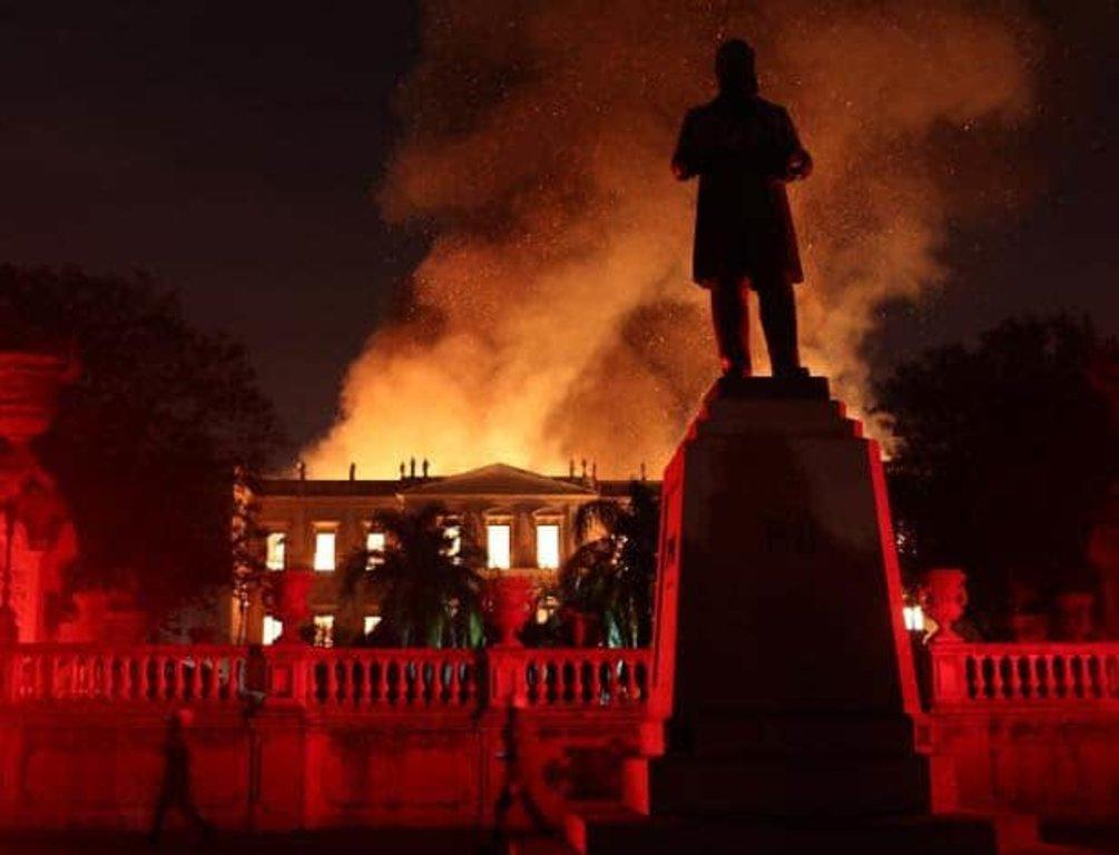 Nosso passado virou cinzas. A silhueta da estátua de D. Pedro II assiste impotente o fogo acabar com 200 anos de história (Foto Marcelo Moraes /Reuters) - Gente de Opinião
